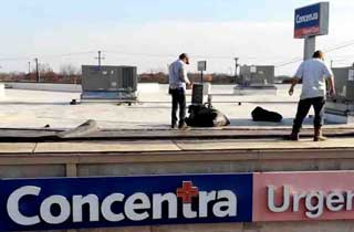 Weathershield roofing employees work on top of  of the Concentra Urgent Care  building in Waco.