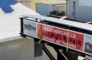 Weathershield truck lift unloading roofing supplies to a local business roof.